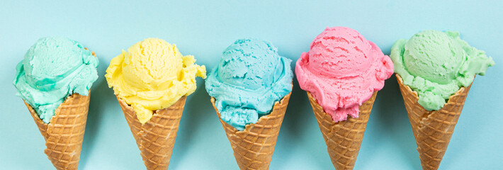 Pastel ice cream in waffle cones, bright background, copy space Wall mural