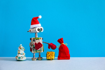 Christmas background. Funny Santa hat robot holds box present and a bag of gifts. Xmas and New Year greeting card frame with robotic toy Santa on blue wall background. Copy text.