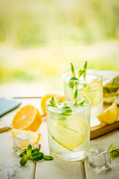 Summer lemonade in glasses in front of window, copy space