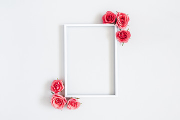 Flowers composition. Rose flowers, photo frame on pastel gray background. Flat lay, top view, copy space