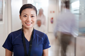 Portrait Of Smiling Female Nurse Wearing Scrubs In Busy Hospital Corridor