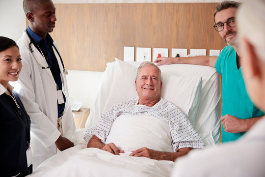 Medical Team On Rounds Meeting Around Bed Of Senior Male Patient