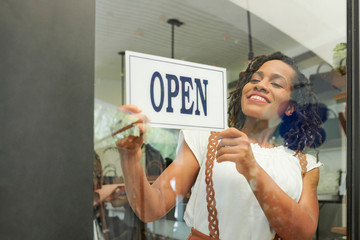 Pretty young Black woman opening her store in the morning