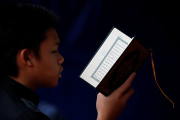 A boy reads the Koran during the holy fasting month of Ramadan at a mosque in Jakarta