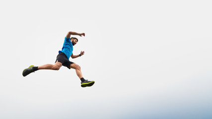 Athlete man running in the mountains during a jump in the sky Wall mural
