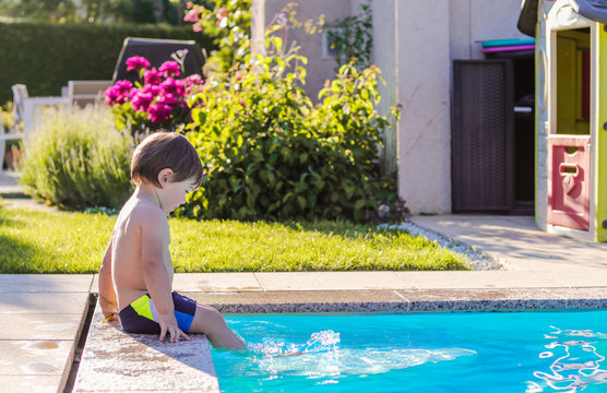 Little happy boy sitting on side of swimming pool in garden playing by his feet in water having fun. Summertime. Summer holidays.