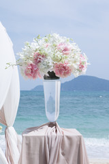View of  nice fresh orchid with roses  on blue  sea back