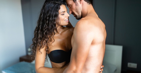 Young couple being intimate in bedroom. Sensual lovers making love in bedroom.