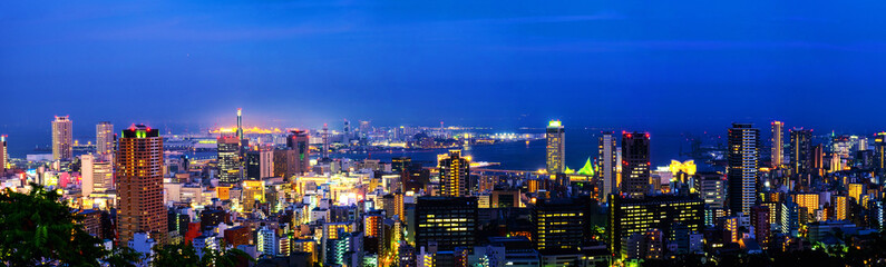 Panoramic aerial view of downtown in Kobe, Japan at night. Blue sky