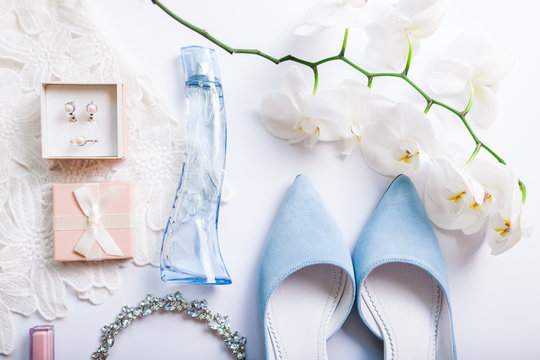 Stylish female wedding clothes, blue shoes and accessories with flowers. Morning of bride