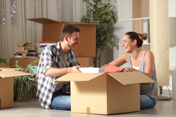 Happy couple laughing unboxing belongings moving house