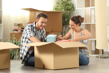 Happy couple unboxing belongings moving home