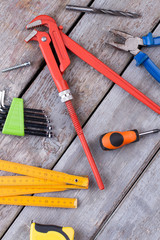 Tools for repair and construction. Screwdriver, pipe wrench pliers, measuring tape, folding ruler, drill bit and screw on wooden background.