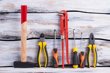 Set of construction tools on wooden background. Hammer, pliers, screwdrivers and an adjustable wrench.