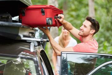 Mann packt Koffer in die Dachbox auf dem Auto