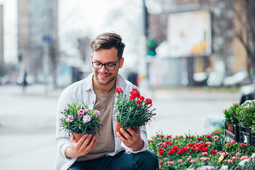 Smiling young man holding two potted plants outdoors, buying flowers. Wall mural