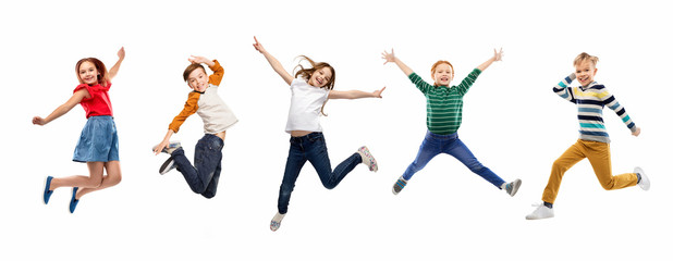 childhood, fun and motion concept - happy children jumping over white background