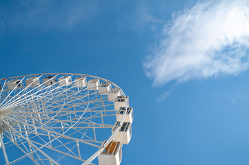 Fototapeta Ferris wheel on blue sky with white clouds background.