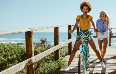Girls having fun with bike on boardwalk Wall mural