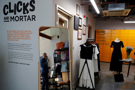 A man is seen reflected in a mirror inside the Amazon-backed pop up store 'Clicks and Mortar' in Manchester