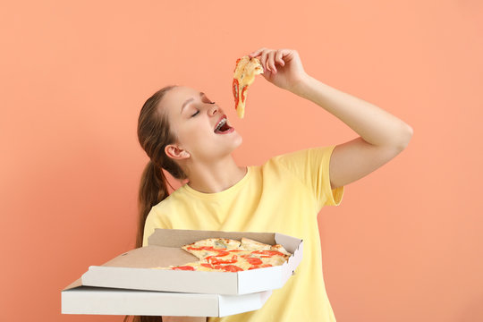 Beautiful woman eating tasty pizza on color background