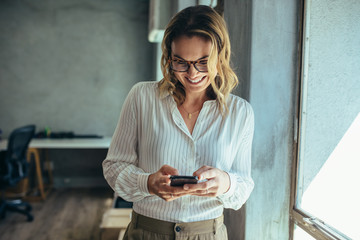 Businesswoman using her smart phone in office Fototapete