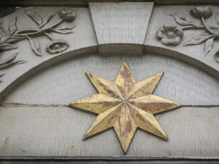 golden star and flowers with leaves in freestone above a door