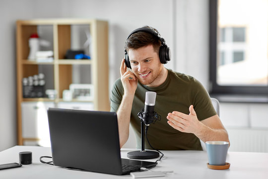 technology, mass media and podcast concept - happy young male audio blogger in headphones with laptop computer and microphone broadcasting at home office