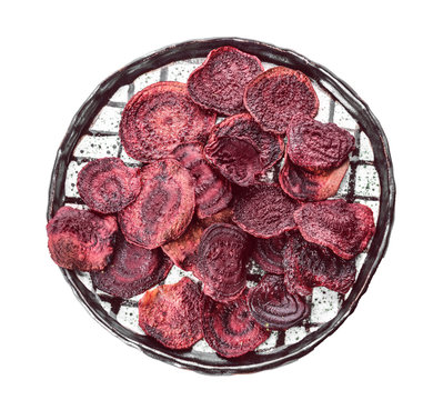 Plate with tasty beet chips on white background