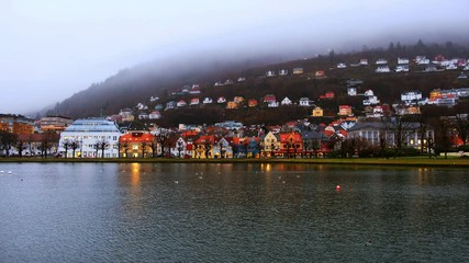 Fototapete - Bergen, Norway. View of old town in Bergen, Norway in the evening. Famous landmarks with pond at sunse with car traffic and clouds over mountains
