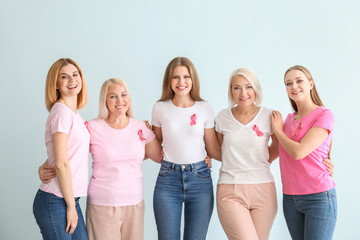 Beautiful women of different ages with pink ribbons on light background. Breast cancer concept