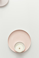 A fresh pear cut in half showing the seeds layed out on a set of pastel powdery rose plates on a light grey table.