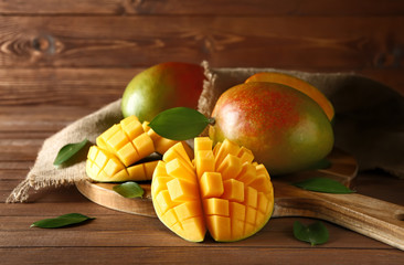 Board with tasty fresh mango on wooden table