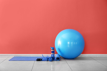 Set of sports equipment with fitness ball and bottle of water near color wall