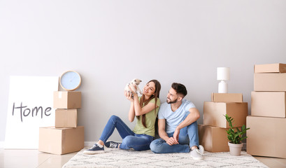 Young couple with belongings and kitten sitting near light wall in their new house