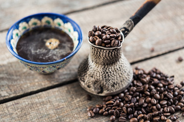 Fotobehang Koffiebonen Coffee beans in a coffeepot or turk on a wooden background