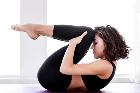 Young slender female is lying at wind relieving pose. Athletic brunette woman in black uniform is practicing yoga, meditating in pavanamuktasana posture at fitness studio. Healthy lifestyle concept.