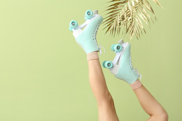 Legs of woman in roller skates and golden tropical leaves on color background