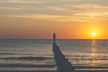 sunset over the baltic sea, young man is balancing on a groin