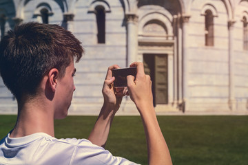 young man taking a photo of the leaning tower of Pisa, Italy