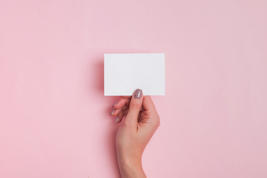 Woman's hand holding blank paper card