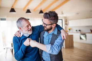 An adult son and senior father indoors at home, making fist bump. Wall mural