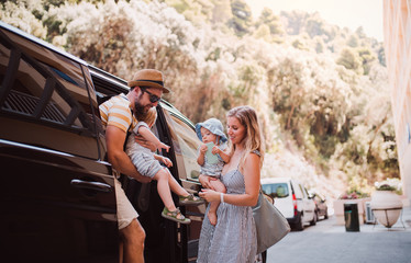 A young family with two toddler children getting out of taxi on summer holiday. Wall mural