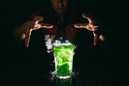 Barman`s hands showing smoking green cocktail