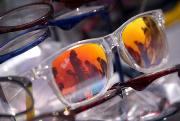 Shoppers are reflected in sunglasses on display for sale at a market ahead of the Muslim festival of Eid al-Fitr in Srinagar