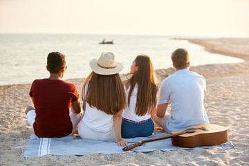 Back view of group of friends sitting together on towel on white sand beach during their vacation and enjoying a sunset above the sea. Men and women relax on the shore with guitar. Tranquil scene. Fototapete
