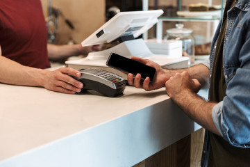 Photo of european man paying cellphone in cafe while waiter holding payment terminal