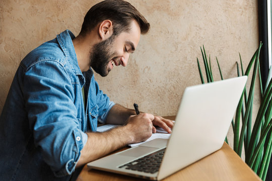 Photo of smiling bearded man writing with laptop while working in cafe indoors