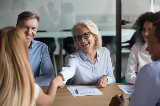Mature businesswoman shaking hand of business partner at meeting
