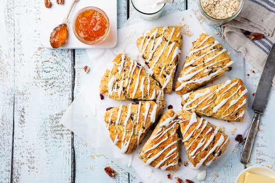 Scones with oats, cranberry and pecan nuts on wooden background. Top view. Copy space.